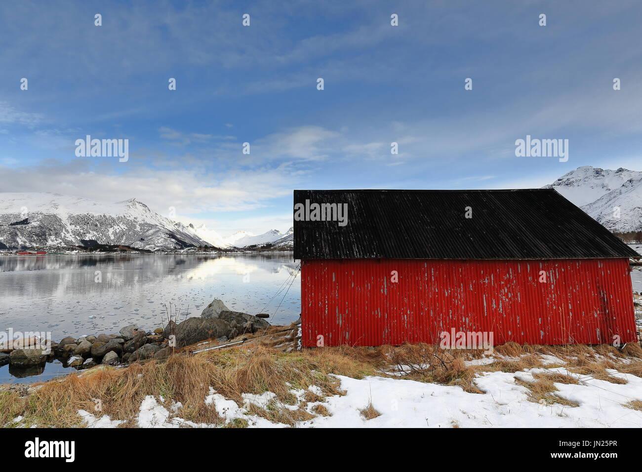 Rolling steel boathouse-red wall-black roof. Gimsoystraumen flow-Olderfjorden mouth. Mts.Kleppstadheia-Kvasstinden-Botntinden-Rismalstindan-Smatindan- - Stock Image