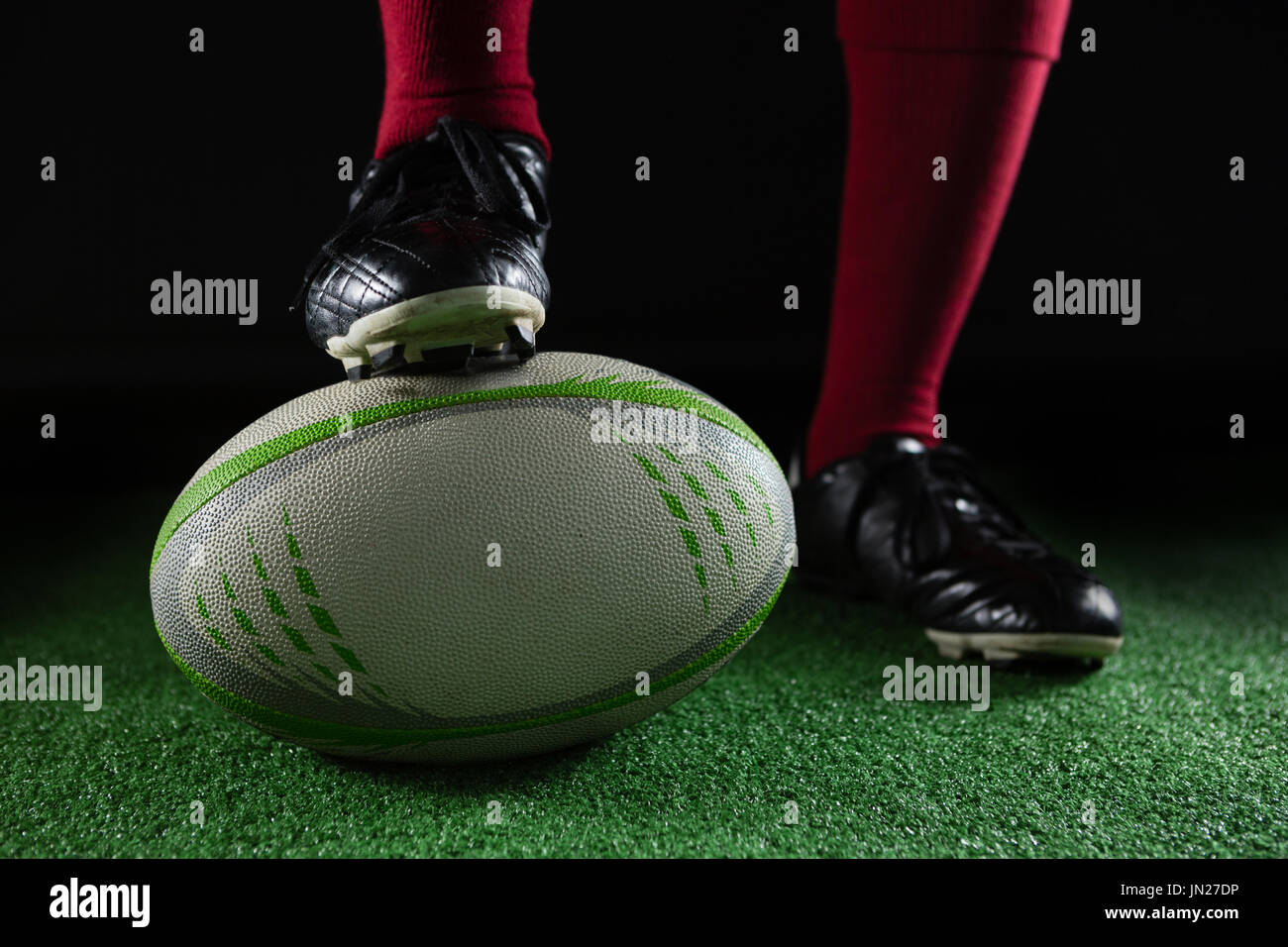 Low section of person stepping on rugby ball while plying rugby - Stock Image