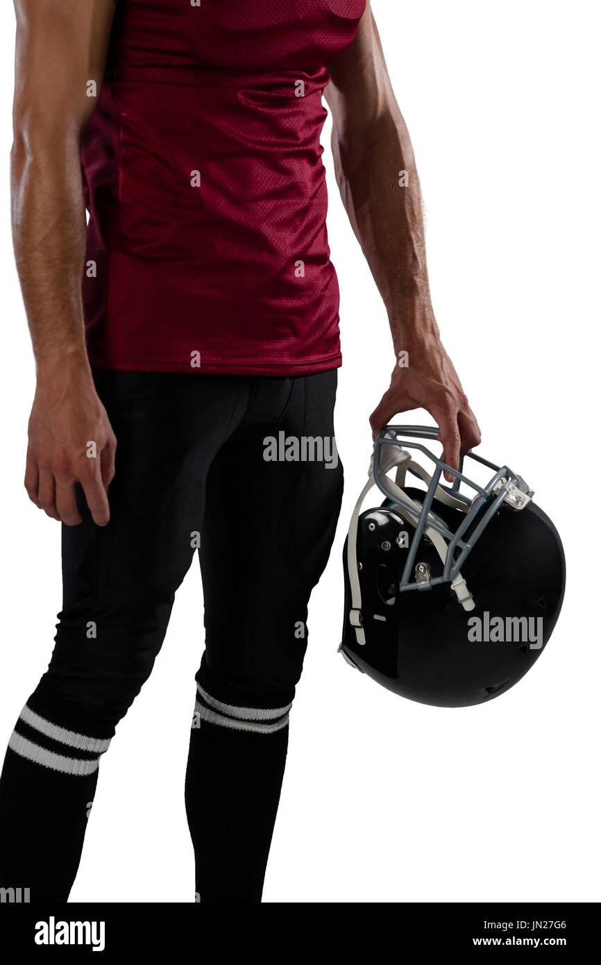 Midsection of sportsperson holding helmet against white background - Stock Image