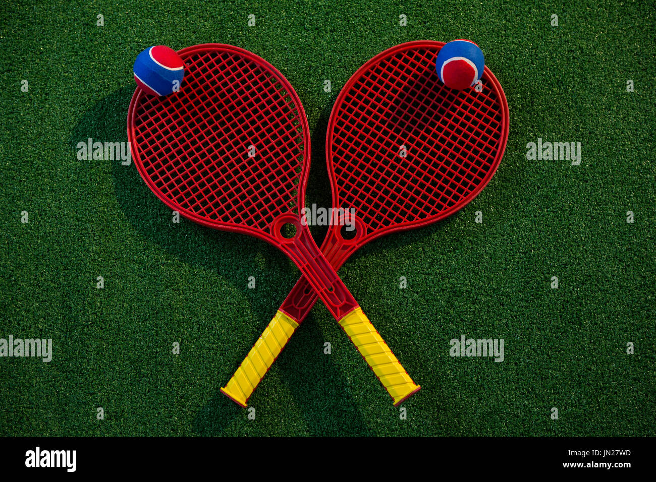 Overhead view of colorful tennis balls on rackets at plying field - Stock Image
