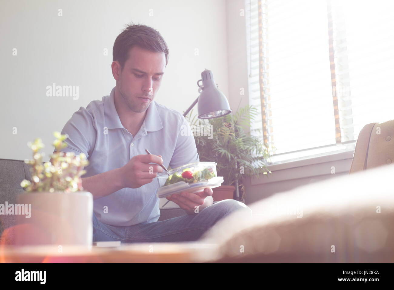 Man having food while sitting on sofa by window at home - Stock Image