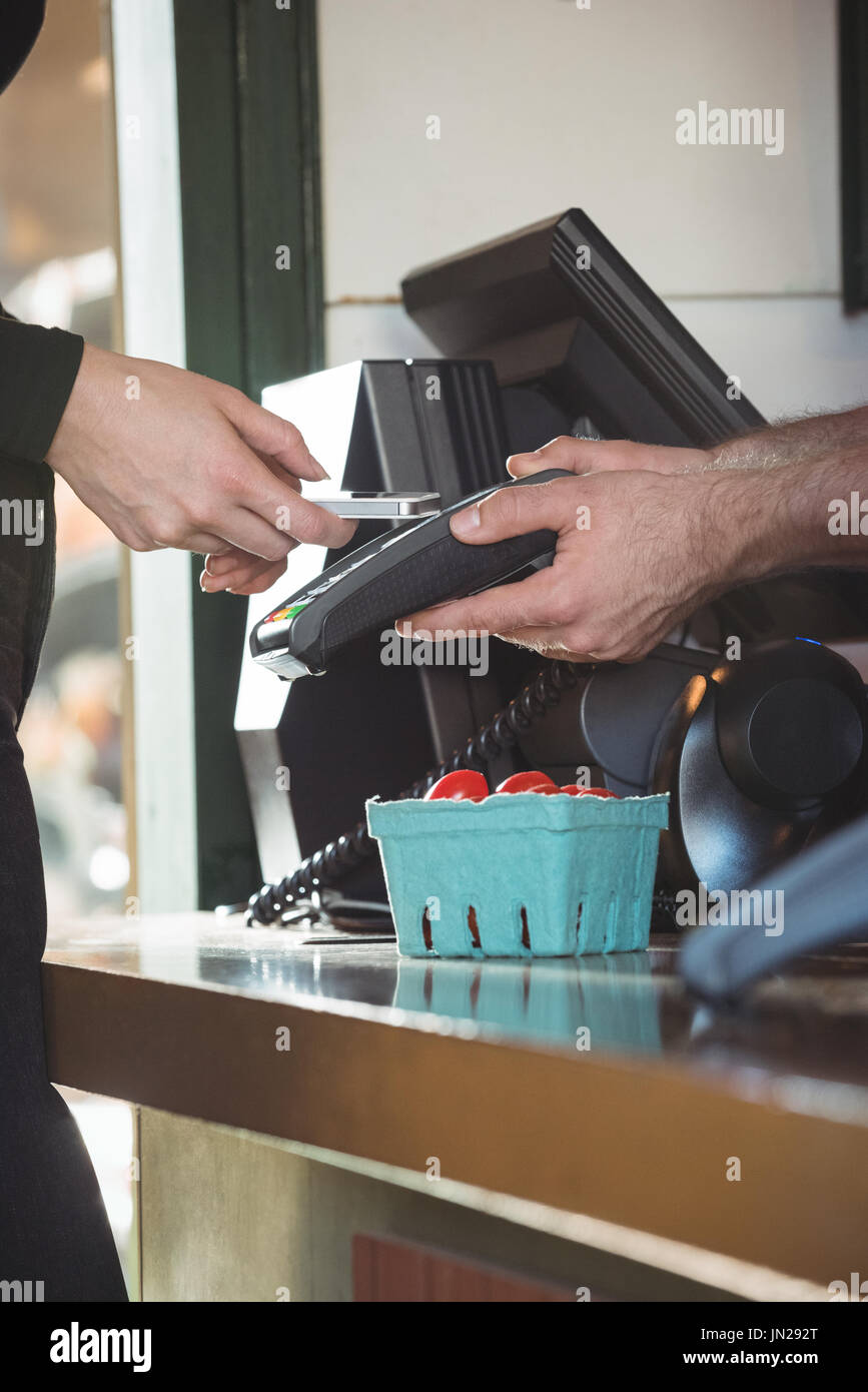 Woman paying bill through smartphone using NFC technology Stock Photo