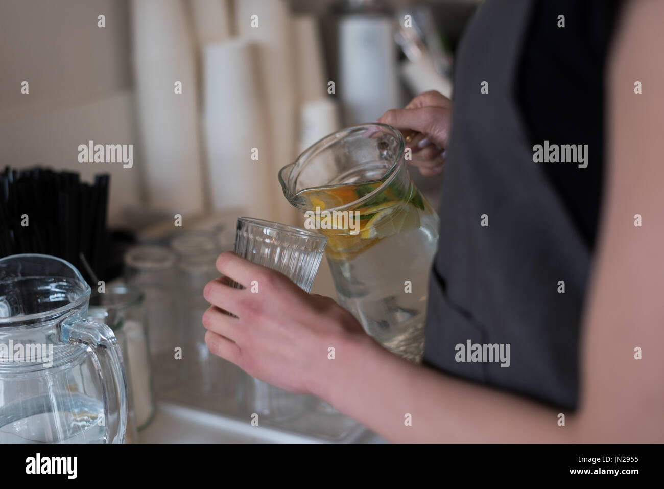 Mid section of woman pouring water in drinking glass while standing in kitchen Stock Photo