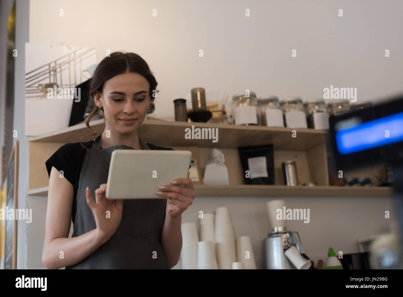 Female owner using digital tablet while standing in kitchen at cafe - Stock Image