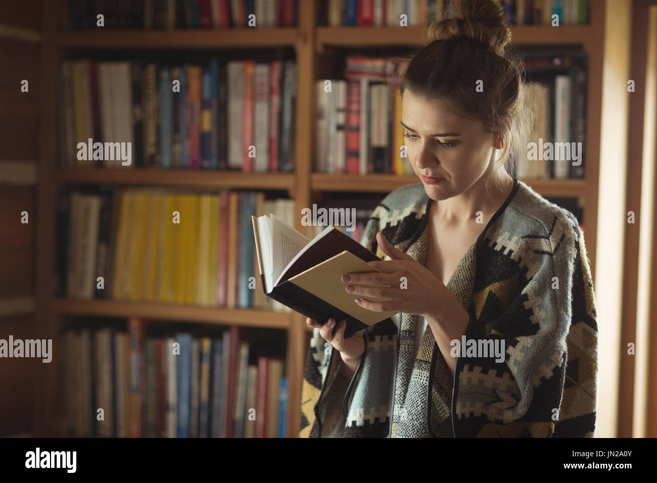 Woman reading book in library at home - Stock Image