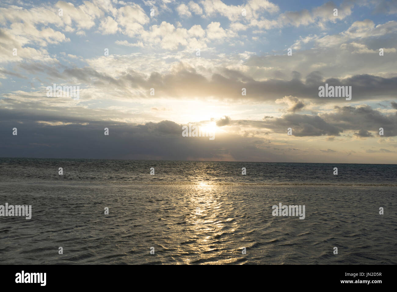 Sunrise with Clouds and Calm waters Stock Photo