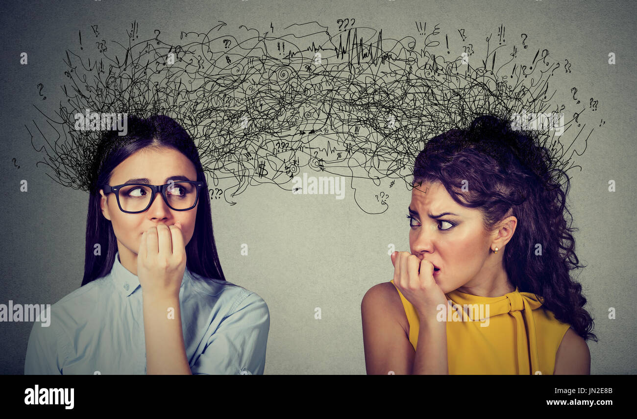Side profile of two preoccupied anxious women looking at each other exchanging with many thoughts - Stock Image
