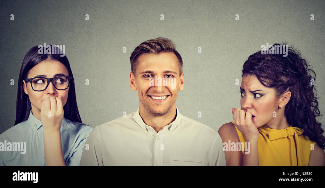 Happy man and two women anxiously looking at him - Stock Image