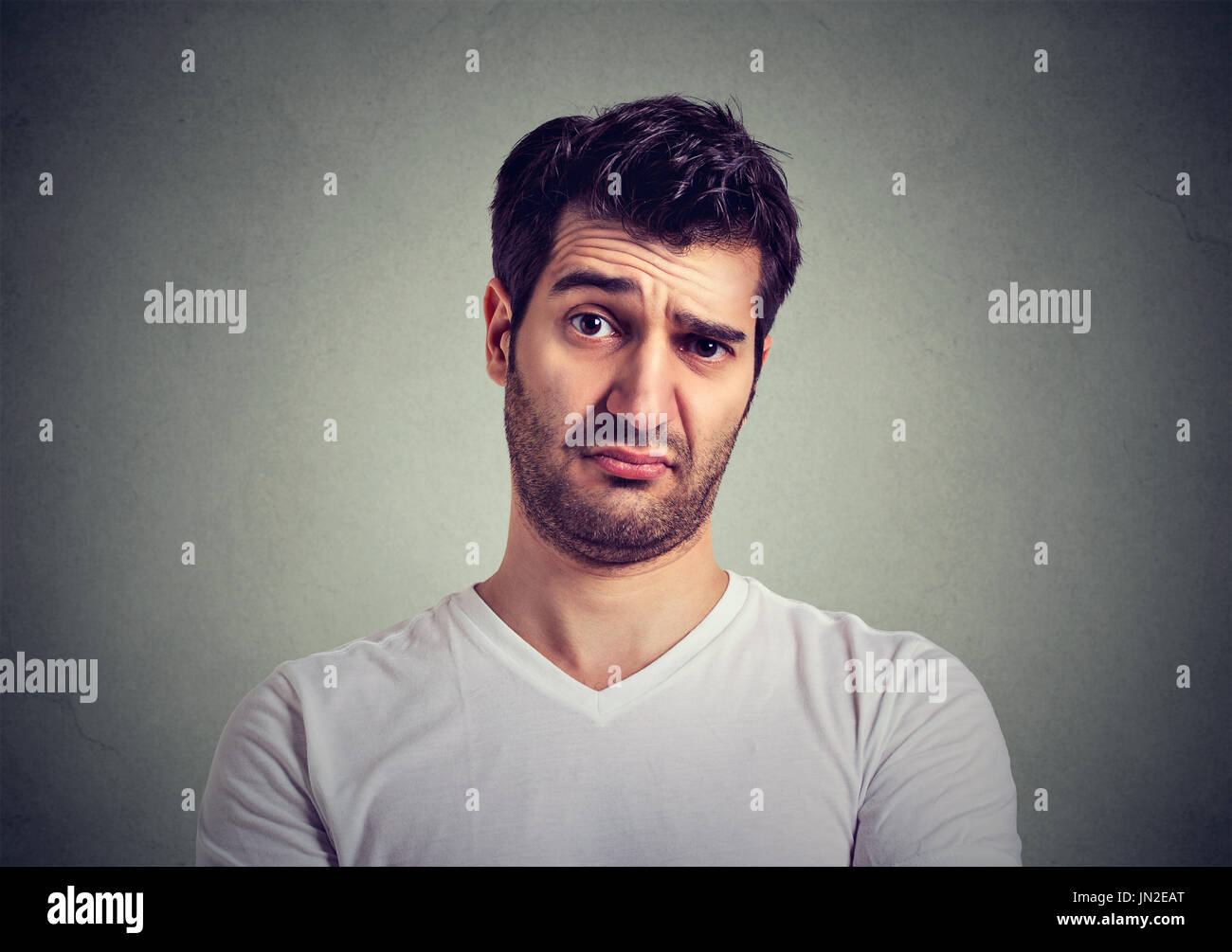 frowning man thinking expressing doubts and concerns - Stock Image