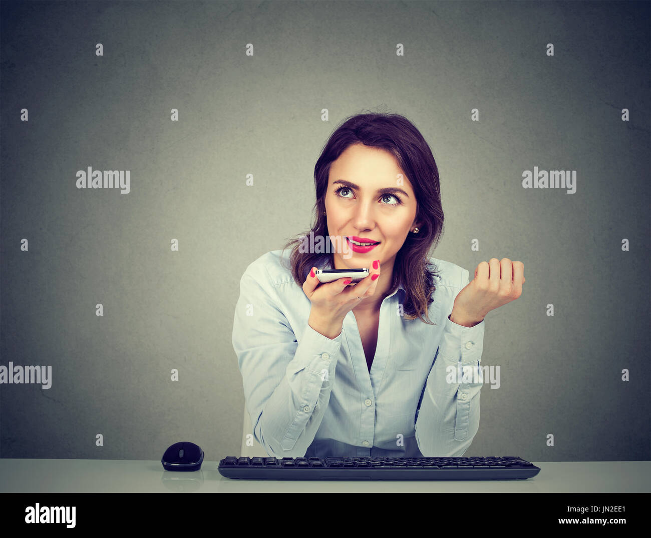 Woman using a smart phone voice recognition function on line sitting at table isolated on gray wall background - Stock Image
