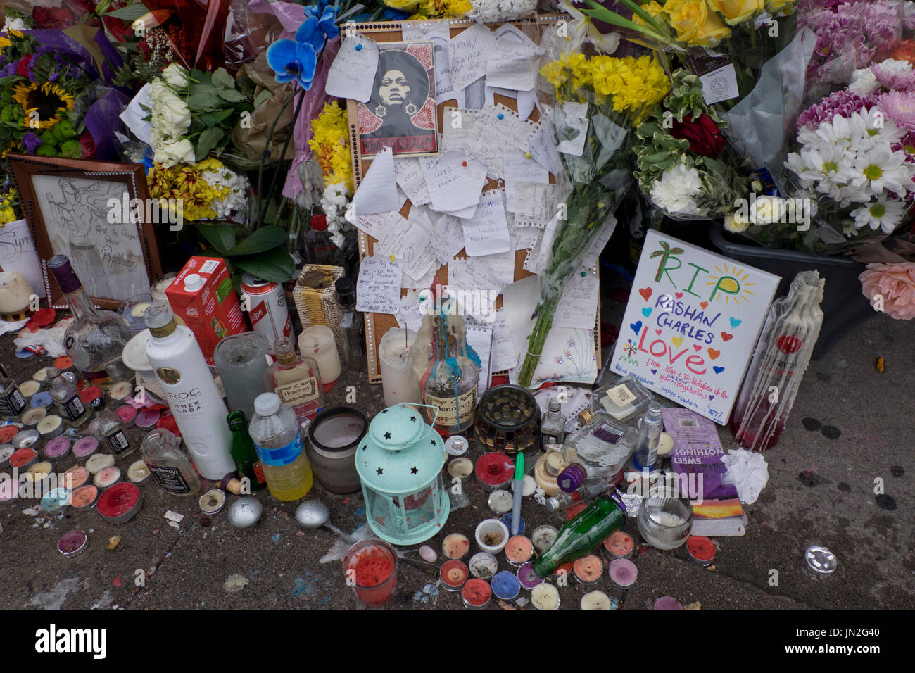 Flowers and messages of defiance outside shop where Rashan Charles, a 20-year-old black man died after being apprehended by police in east London - Stock Image