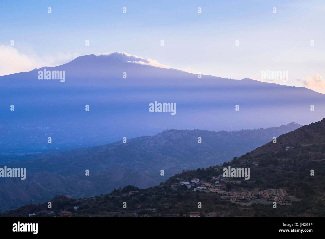 Etna Sicily, rays of the setting sun stream across Mount Etna and the hills surrounding Taormina in Sicily. - Stock Image