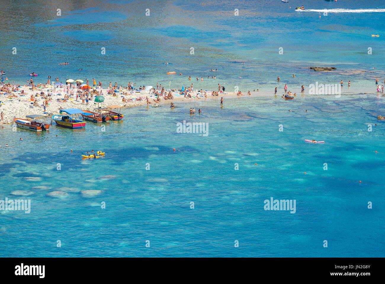 Mazzaro beach Sicily, view in summer of Mazzaro beach, a popular location near to Taormina for those keen to sunbathe or swim, Sicily. Stock Photo