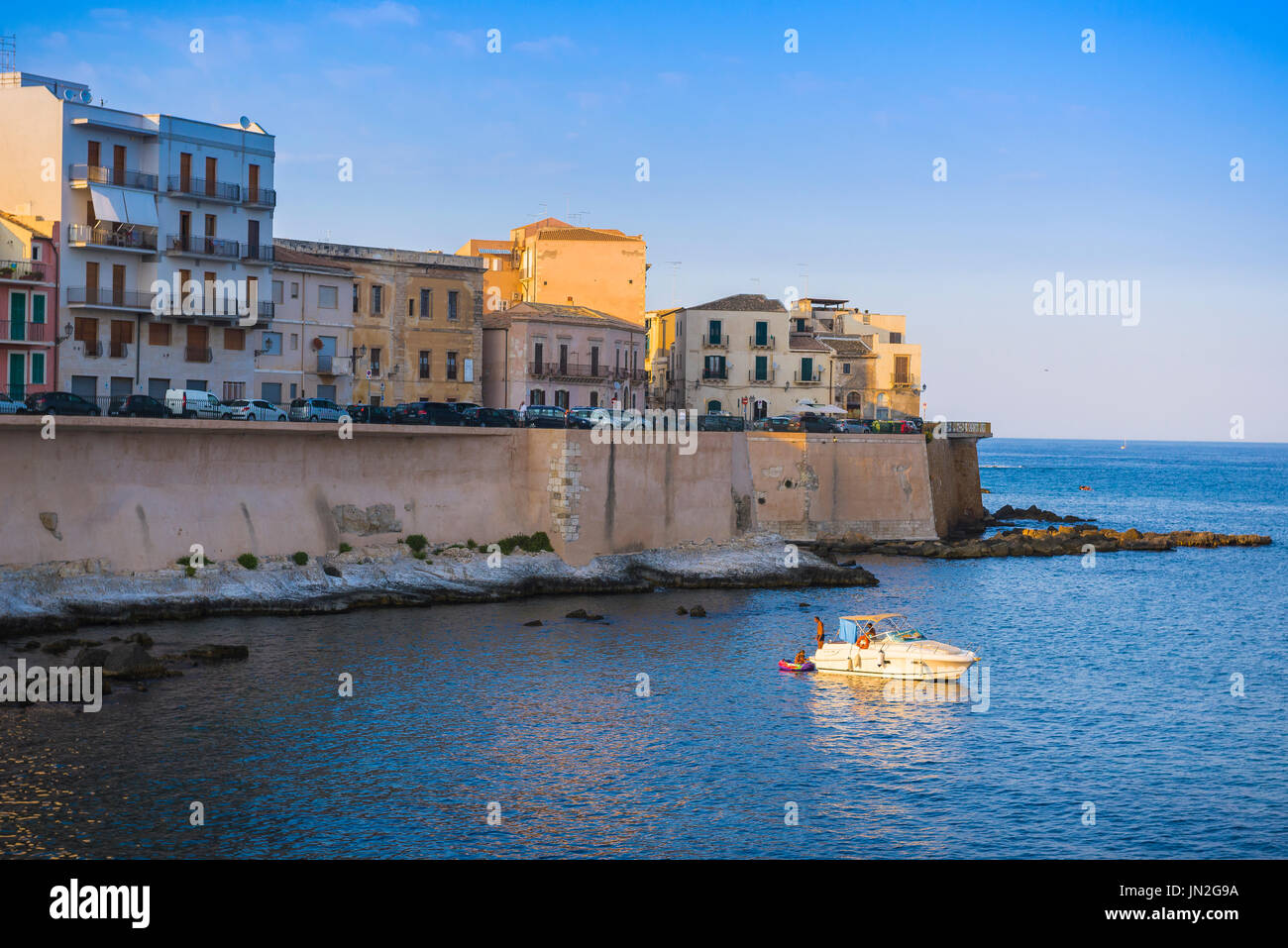 Sicily bay, at sunset in a small bay to the south of Ortigia Island (Syracuse) Sicily, a family relax on a leisure boat. - Stock Image