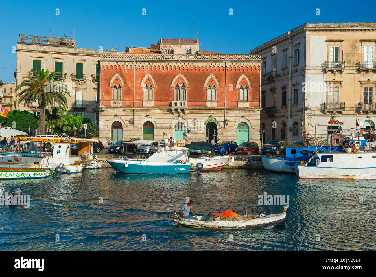 Sicily fishing boat, a fisherman steers his skiff along the Darsena Channel separating the city of Syracuse from Ortigia island, Sicily. - Stock Image