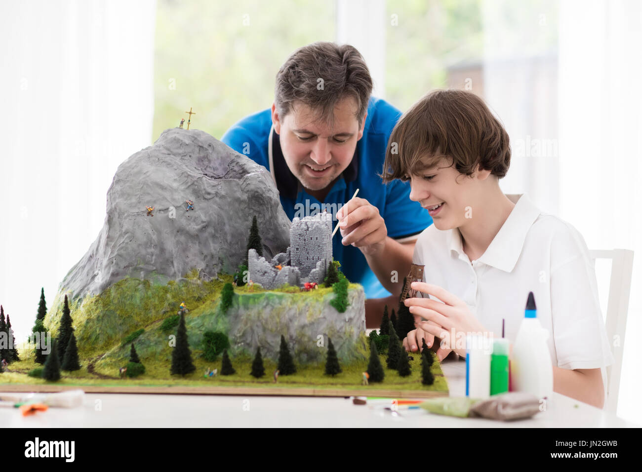 Father and son work on model building school project. Kids and parent build miniature scale model mountain for geography class. Extracurricular activi - Stock Image