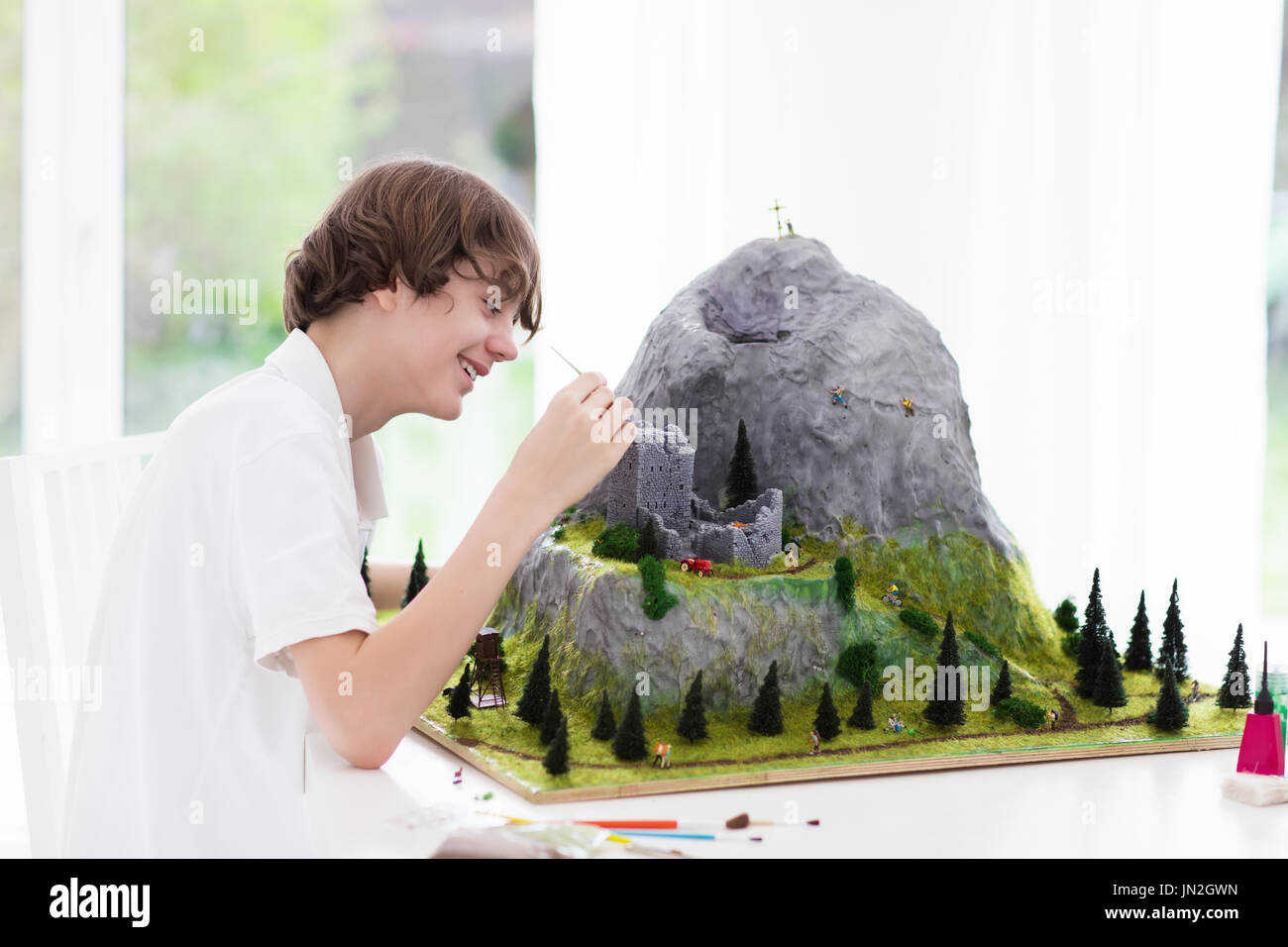 Teenager working on model building school project. Kids build miniature scale model mountain for geography class in high school. Extracurricular activ - Stock Image