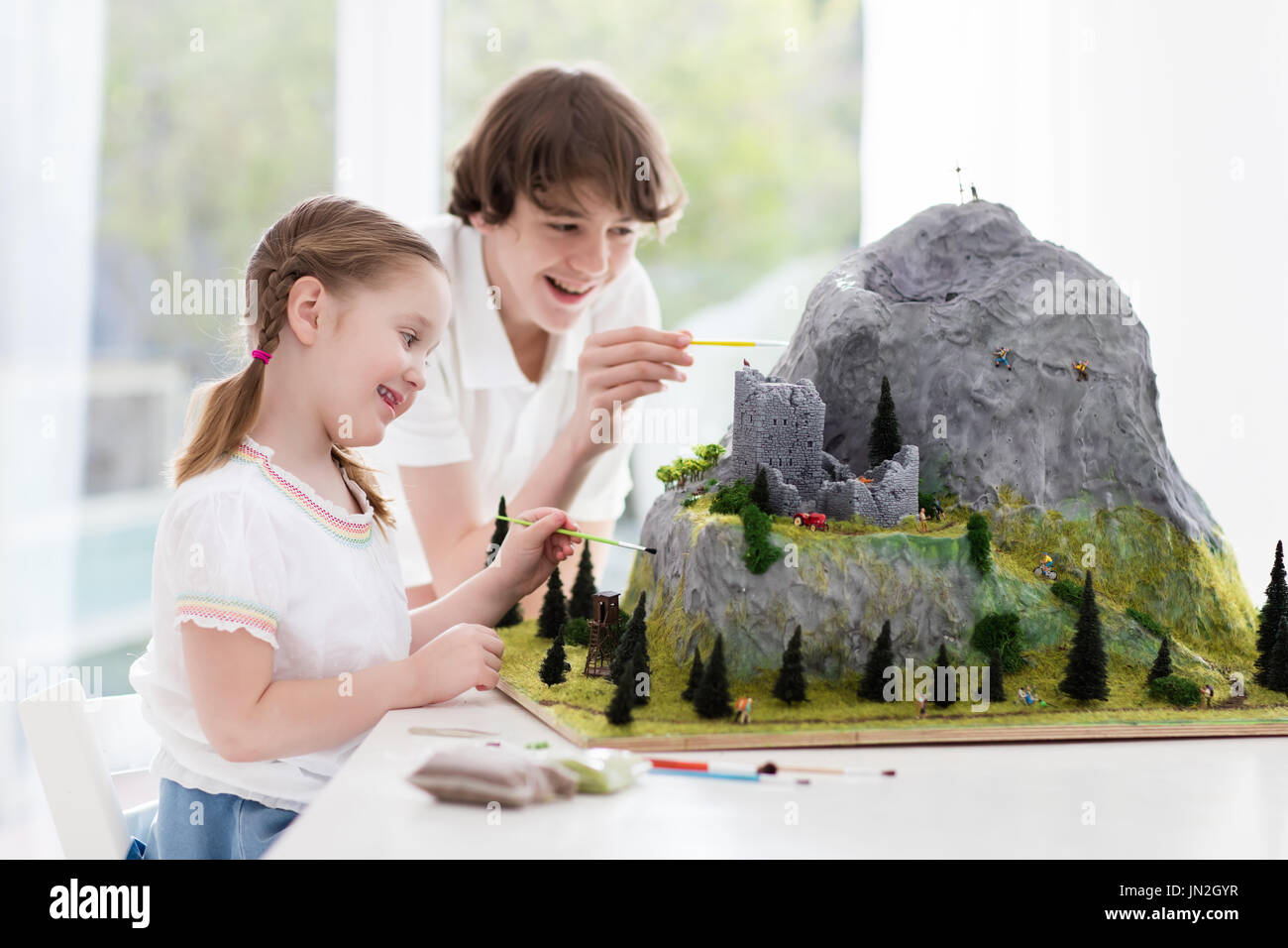 Children work on model building school project. Kids build miniature scale model mountain for geography class. Extracurricular activities and hobby cl - Stock Image
