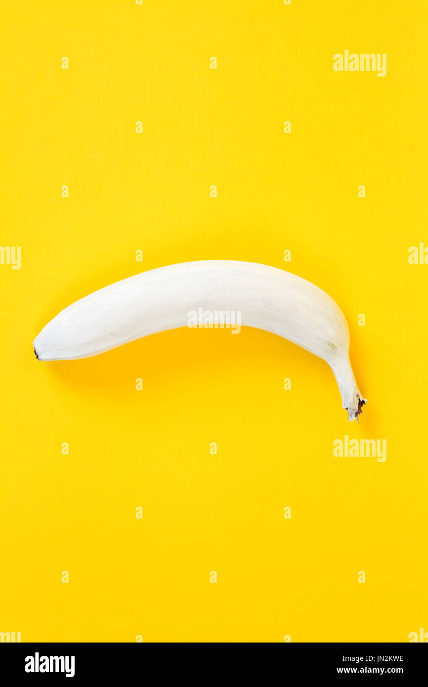 a white banana on a yellow background. Colors have been reversed. Fun, minimal and quirky color still life photography - Stock Image