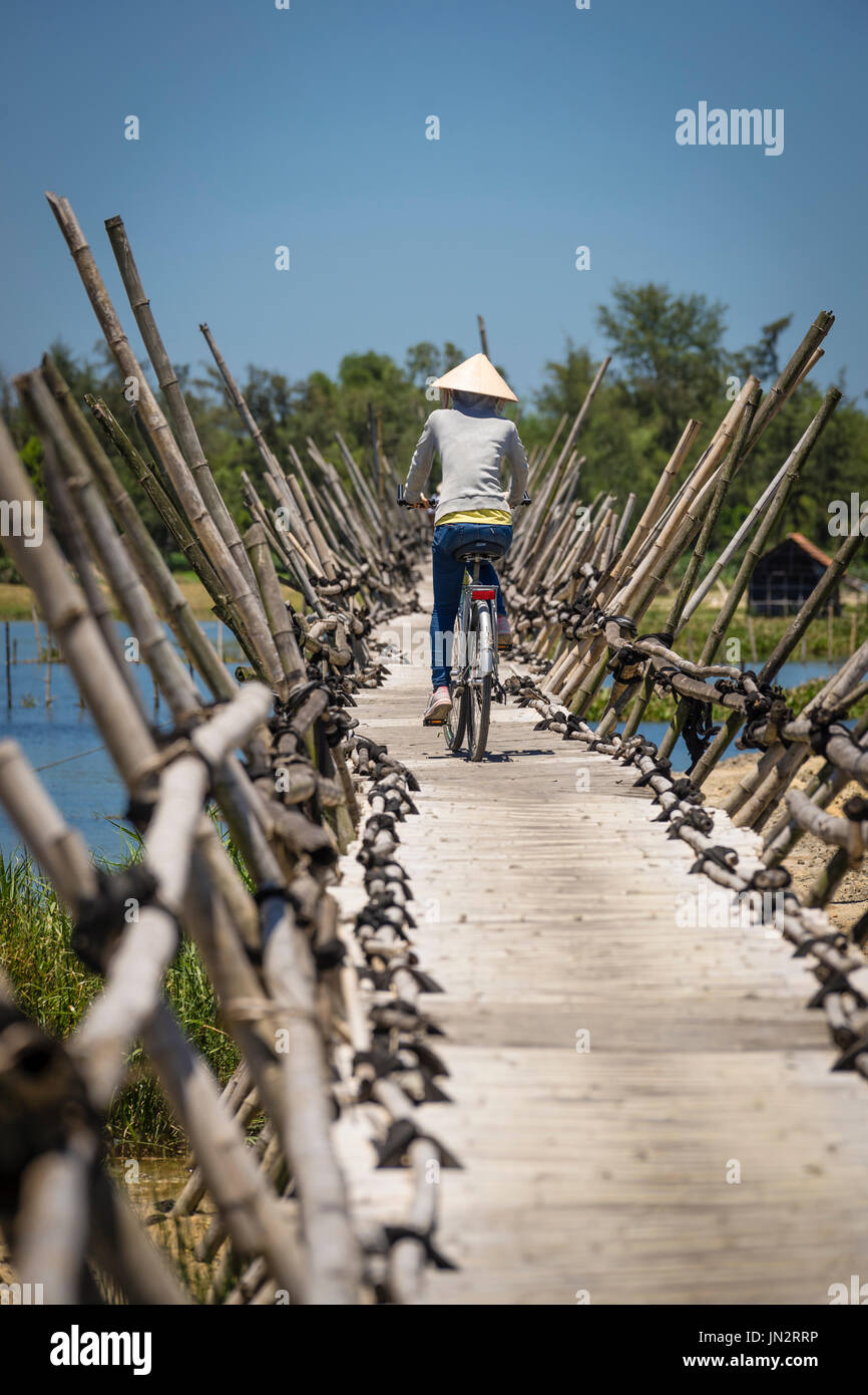 Vietnamese woman bicycling over traditional bamboo bridge in rural Vietnam near Hoi An - Stock Image