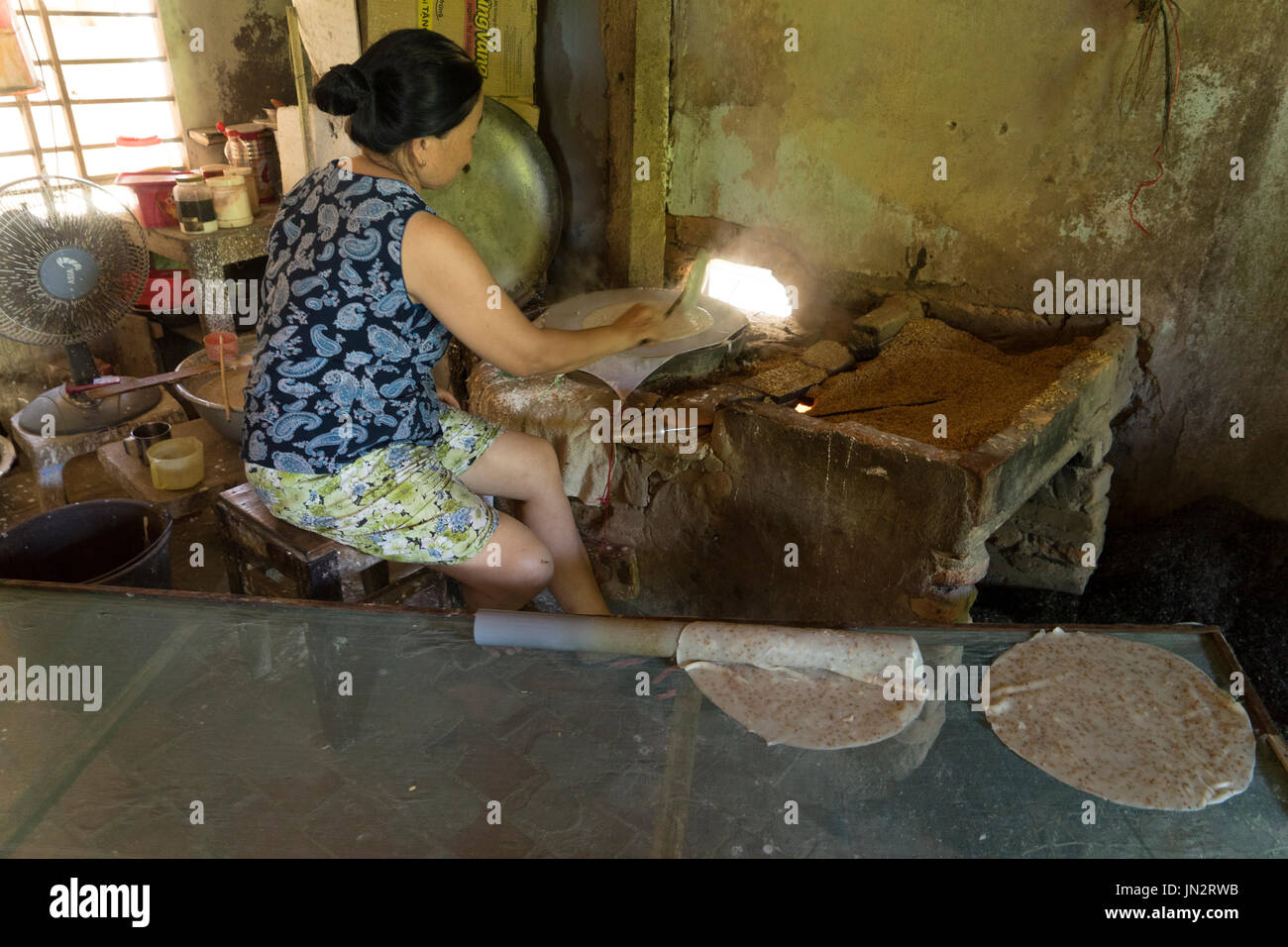 Rural Vietnamese woman cooking rice paste over a wood stove to make rice noodles and crackers - Stock Image