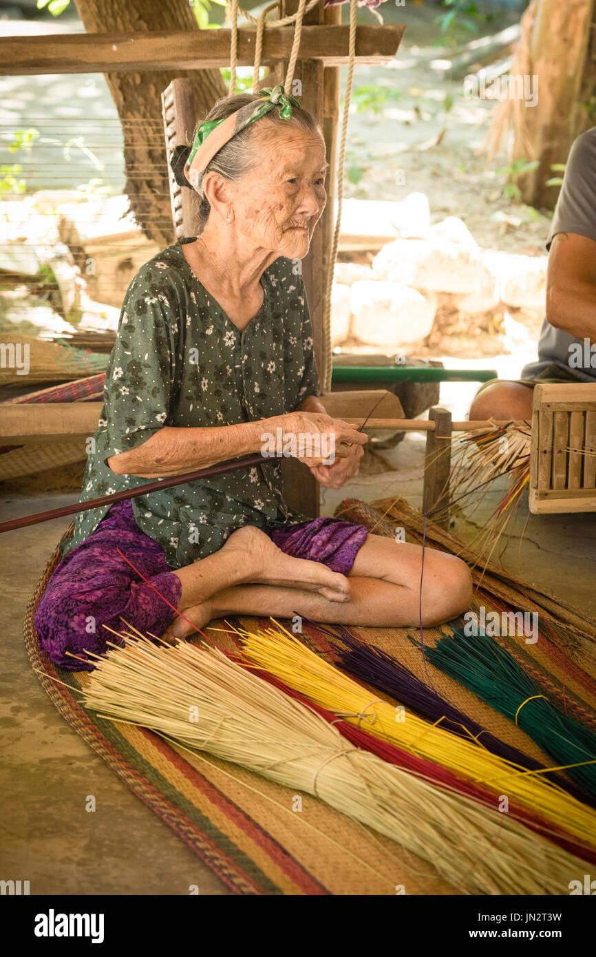 90-year-old Vietnamese woman making reed mats using traditional methods - Stock Image