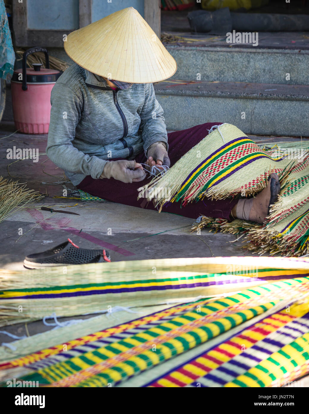 Vietnamese woman in conical hat weaving traditional reed mat - Stock Image