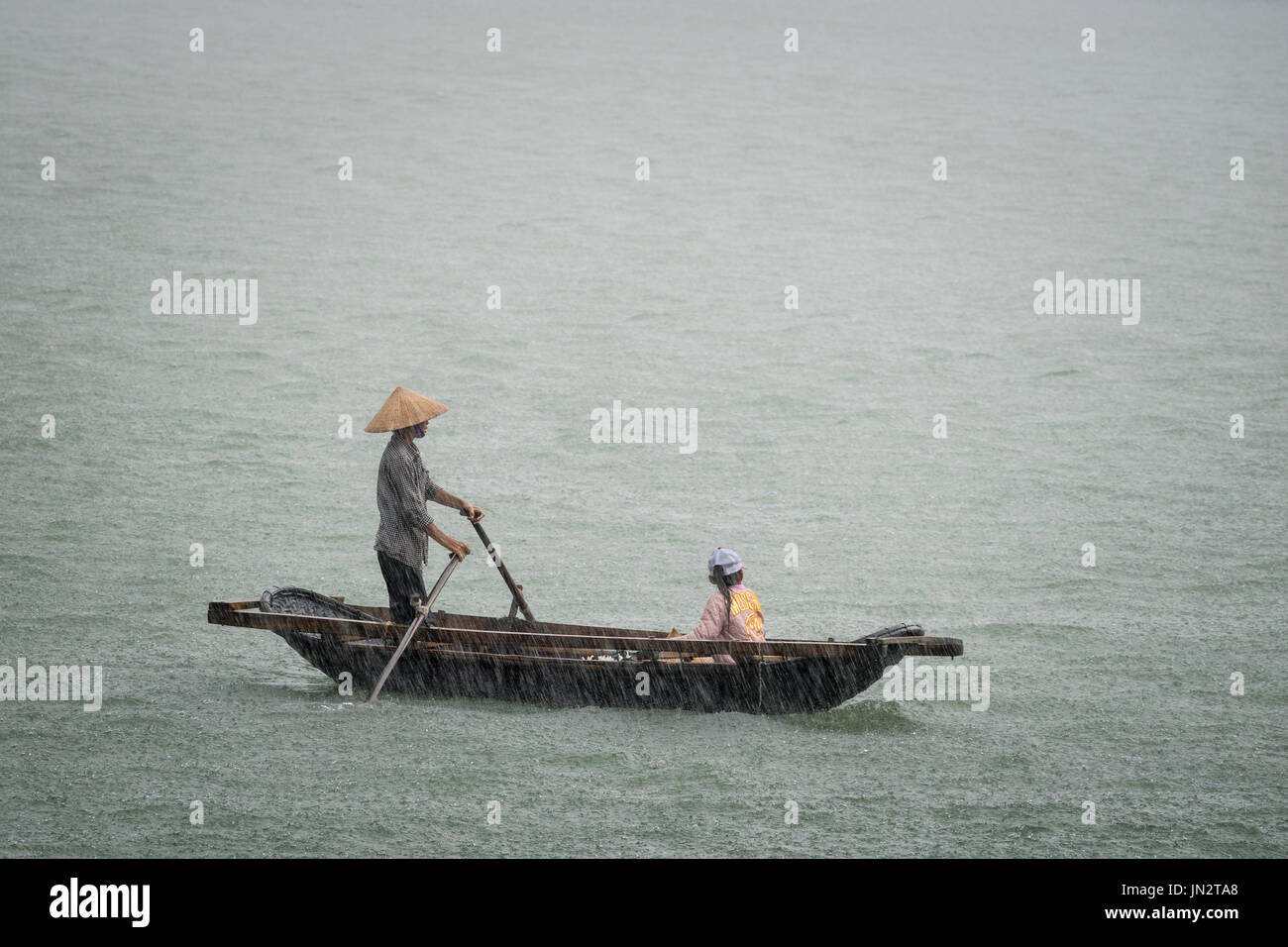 Vietnamese father and daughter in a row boat caught in the pouring rain during a storm at sea - Stock Image