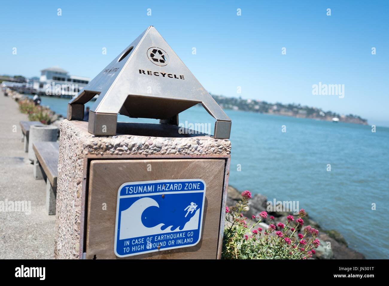 Signage on the side of a trash can reads Tsunami Hazard Zone on Bridgeway Road in the San Francisco Bay Area town of Sausalito, California, June 29, 2017. Tsunamis are a threat to the seismically active Bay Area. - Stock Image