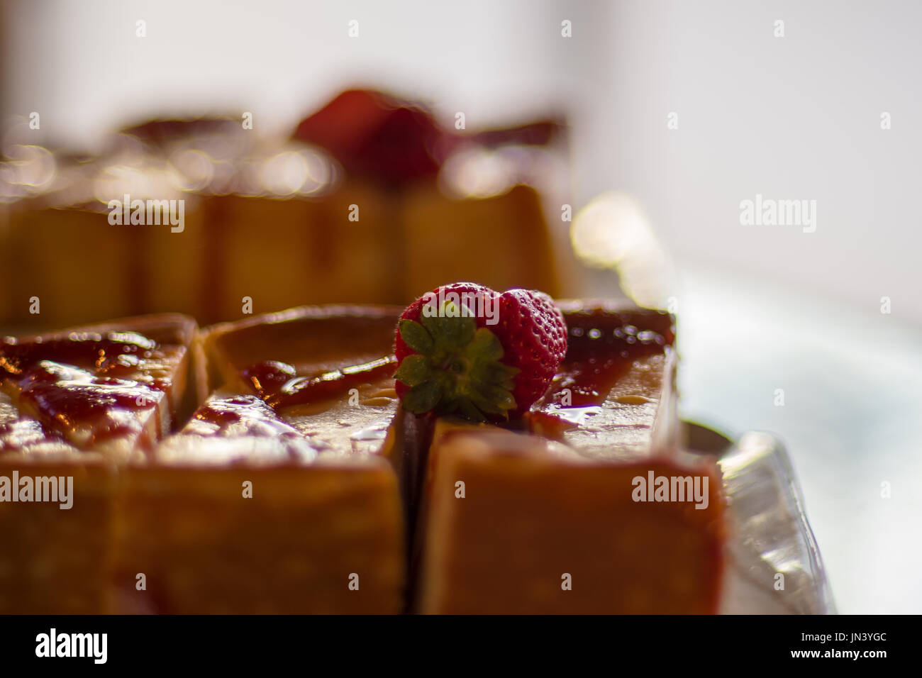 Strawberry cheesecake in close-up shot with blurry background bokeh. - Stock Image