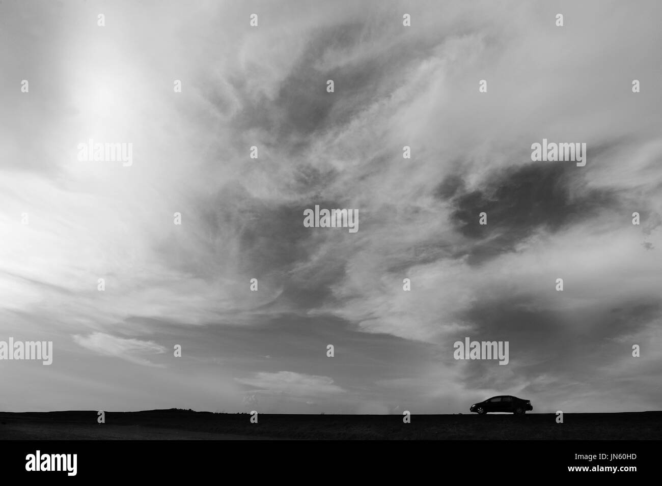 Wide sky and sillhouette car, good for background and slide presentation, minimalism style black and white image. - Stock Image