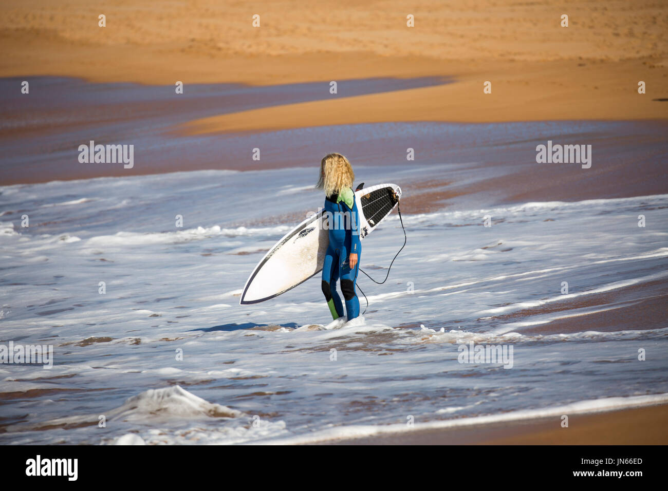 Blonde australian lady in a wetsuit heading to the surf carrying a surfboard,Sydney,Australia - Stock Image