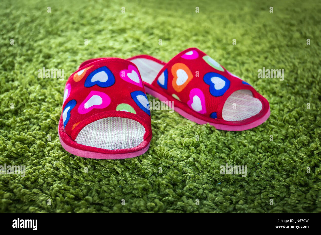 pair of women's Slippers under a warm room light from the window. Pink slippers on green doormat background. The comfort of home. - Stock Image