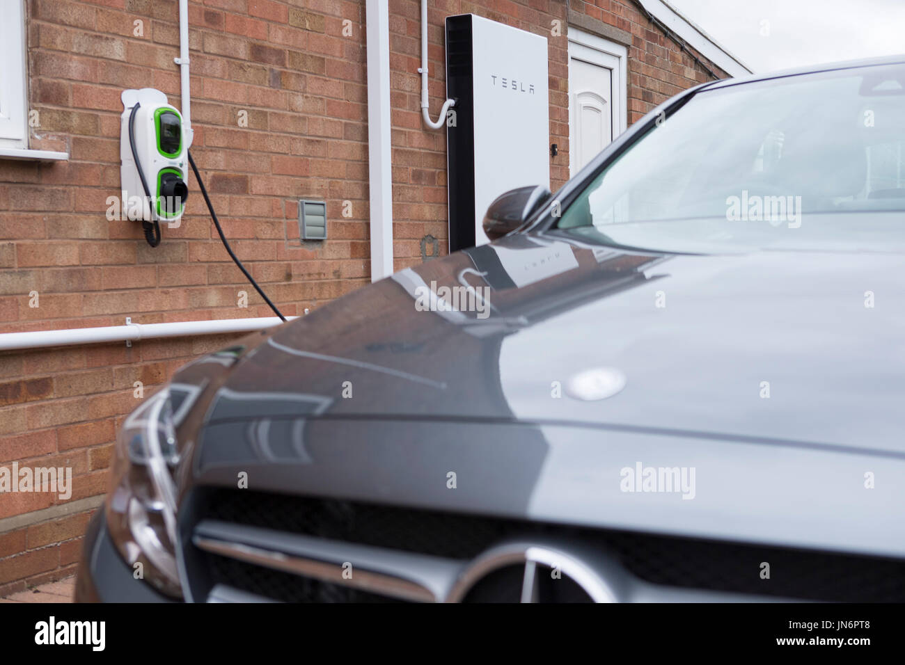 A Mercedes C class Hybrid electric car being charged ( via a Rolec charger) from solar PV stored in a Tesla Powerwall Stock Photo