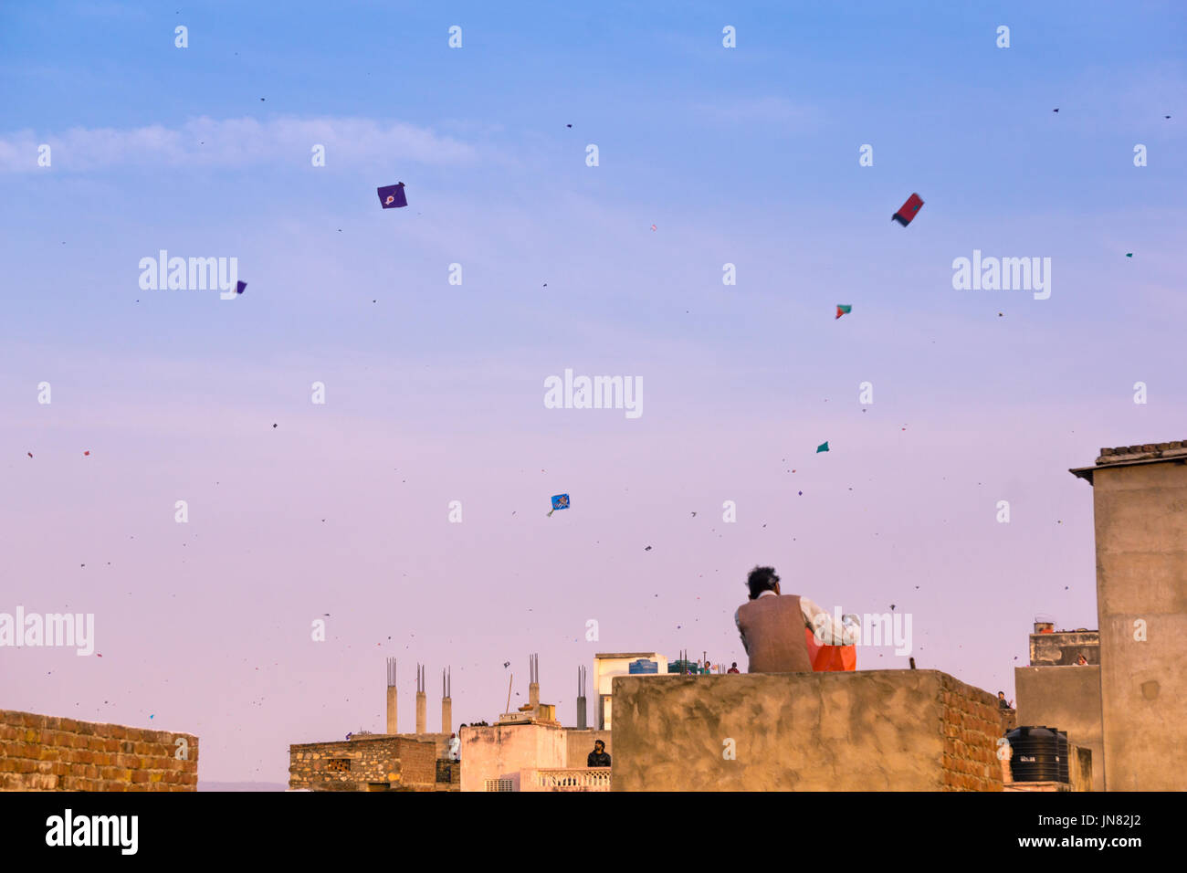 Jaipur, India - 14th Jan 2017 : Families flying kites from the rooftops of their old brick buildings in the old city of Jaipur. This is a popular sport of Makar Sankranti and Independence Day. - Stock Image