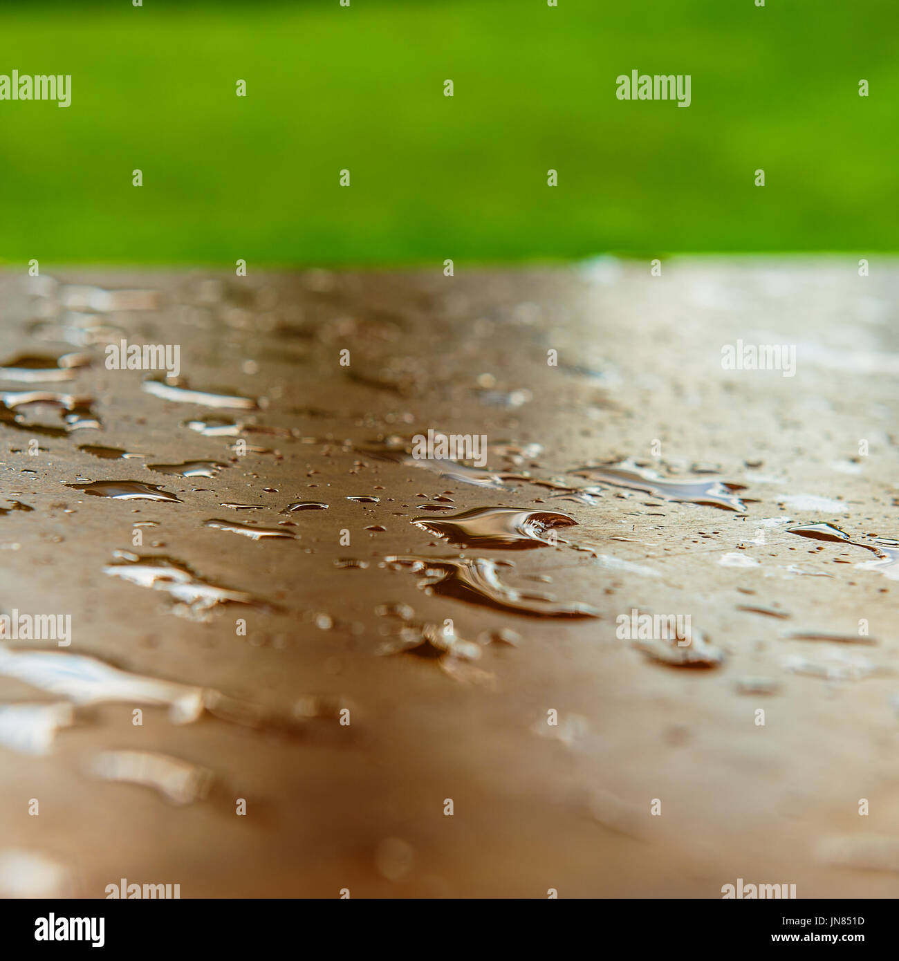 drop of water on the surface of the table and a blurred green background - Stock Image