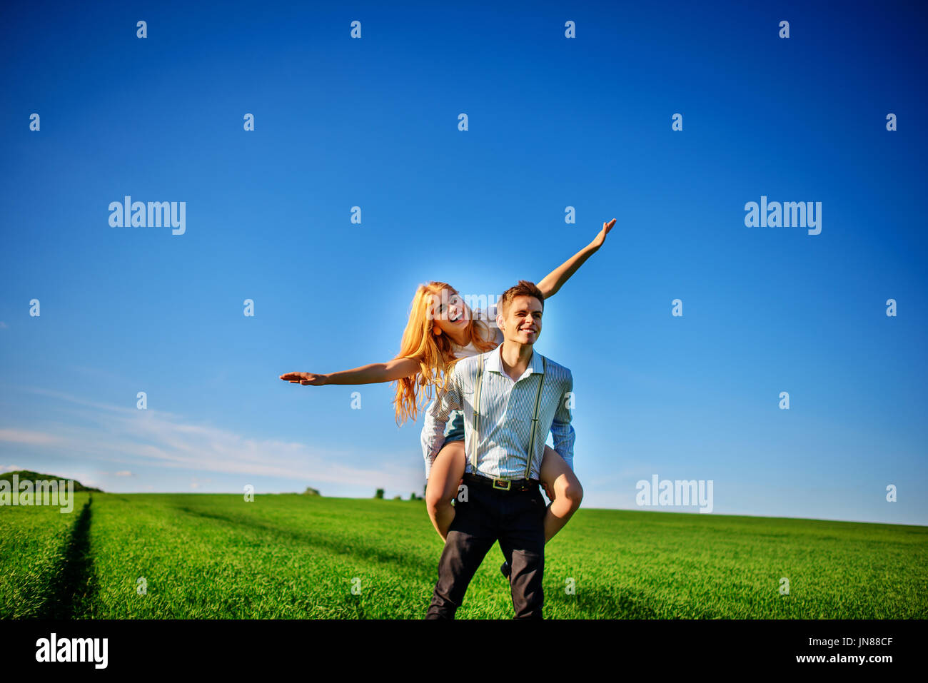Smiling Man is holding on his back happy woman, who pulls out her arms and simulates a flight against the background Stock Photo