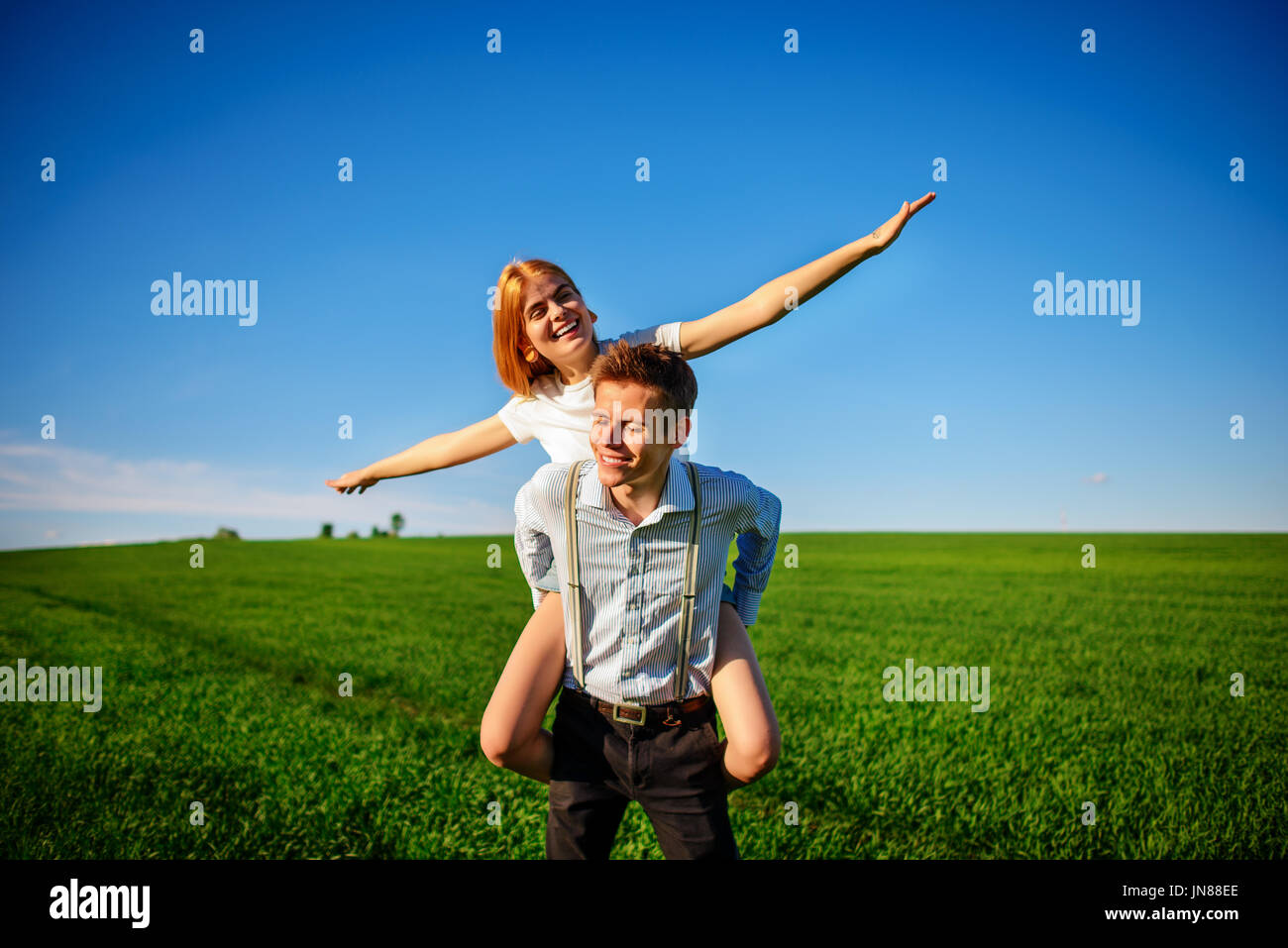 Smiling Man is holding on his back happy woman, who pulls out her arms and simulates a flight against the background of the blue sky and the green fie - Stock Image