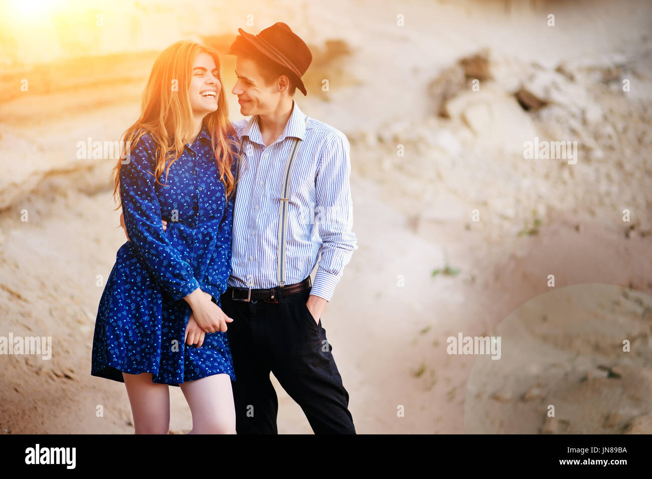 An attractive man hugs a beautiful woman in a blue dress in the middle of a sandy canyon. Lovers are happy, they are smiling to each other. - Stock Image