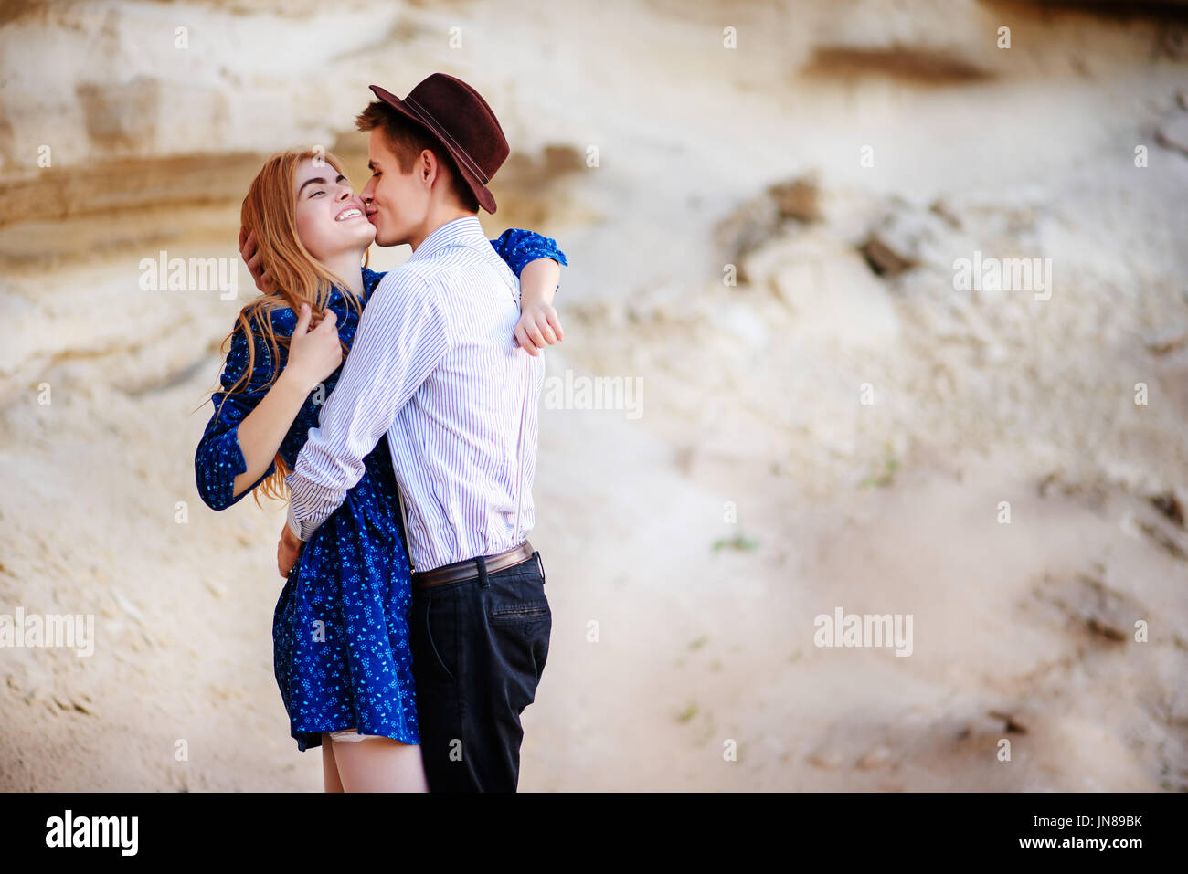 An attractive man is hugging and kissing an beautiful woman in a blue dress in the middle of a sandy canyon. - Stock Image
