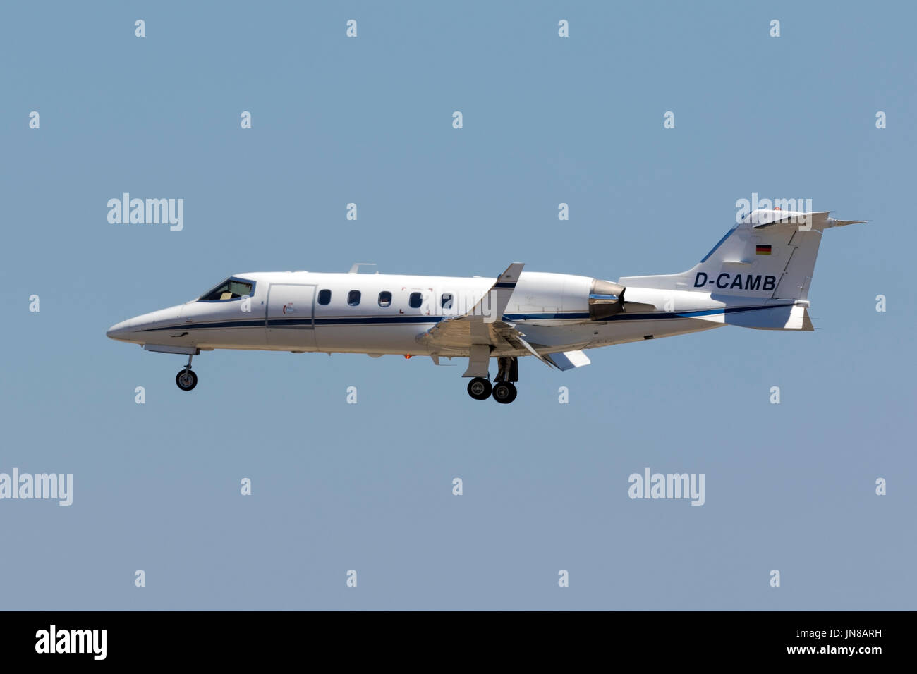 A private German registered Learjet 31A [D-CAMB] on final approach in the hot midday sun. - Stock Image