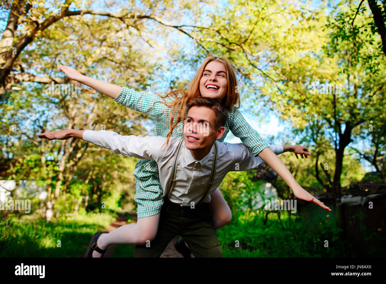 Portrait of happy couple raising their hands in open air. - Stock Image