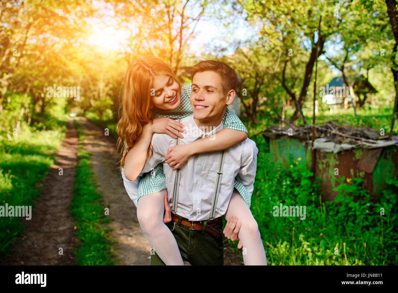 Portrait of young man giving beautiful woman piggyback. - Stock Image