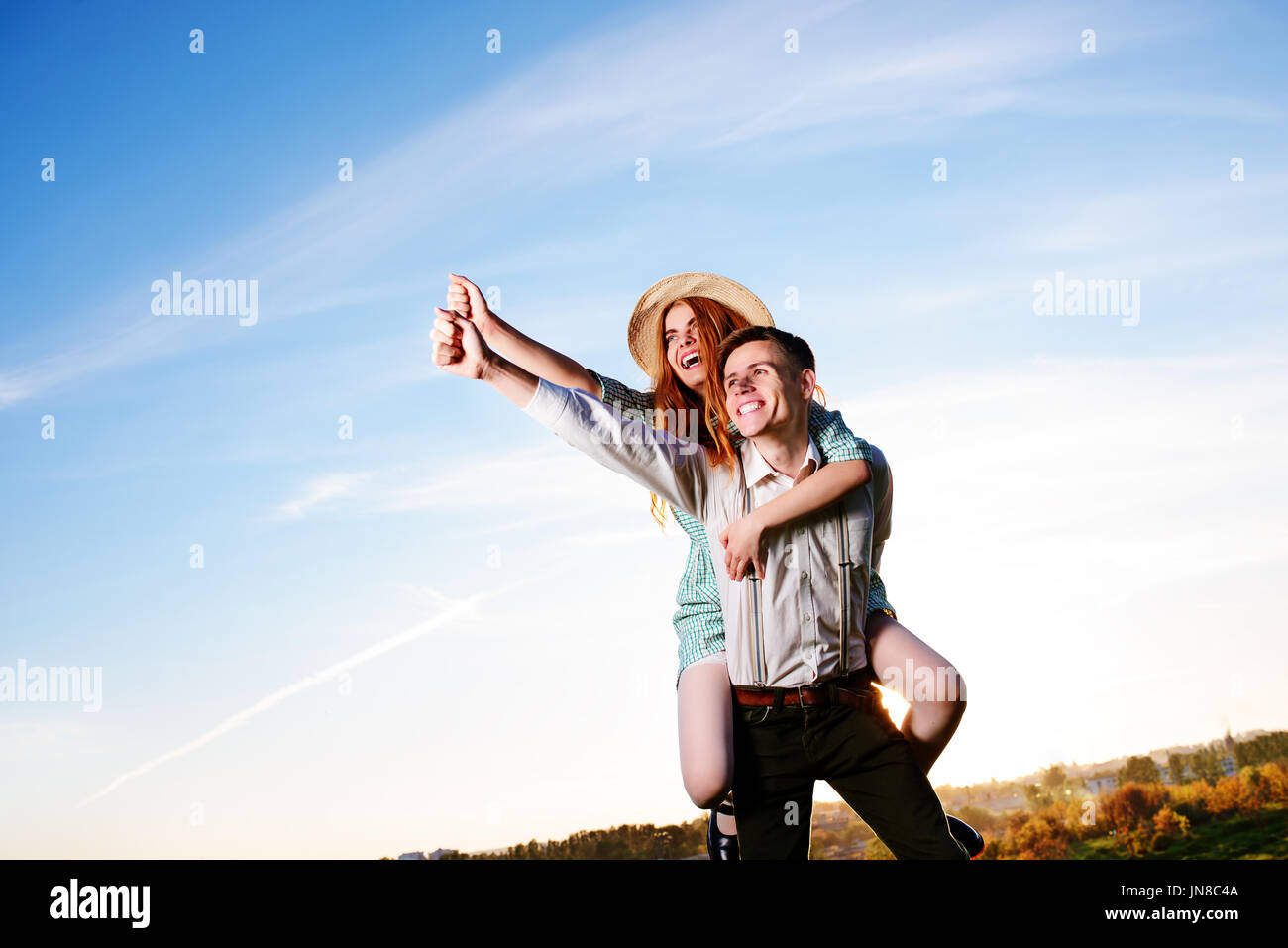 Young man piggybacking his happy girlfriend with raised hand. Cheerful lovers dreaming. - Stock Image