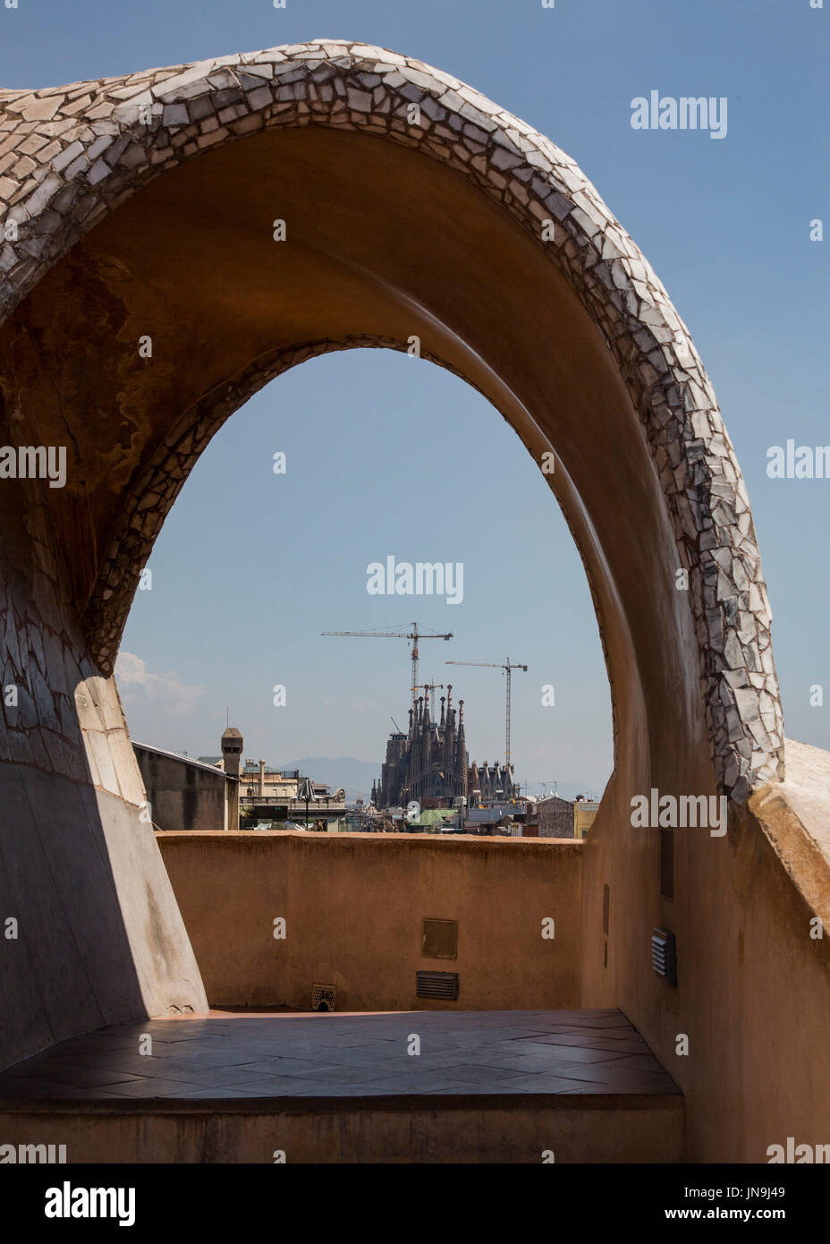 the unfinished Sagrada Familia cathedral designed by Gaudi seen through an archway on the roof of Casa Mila, or Stock Photo