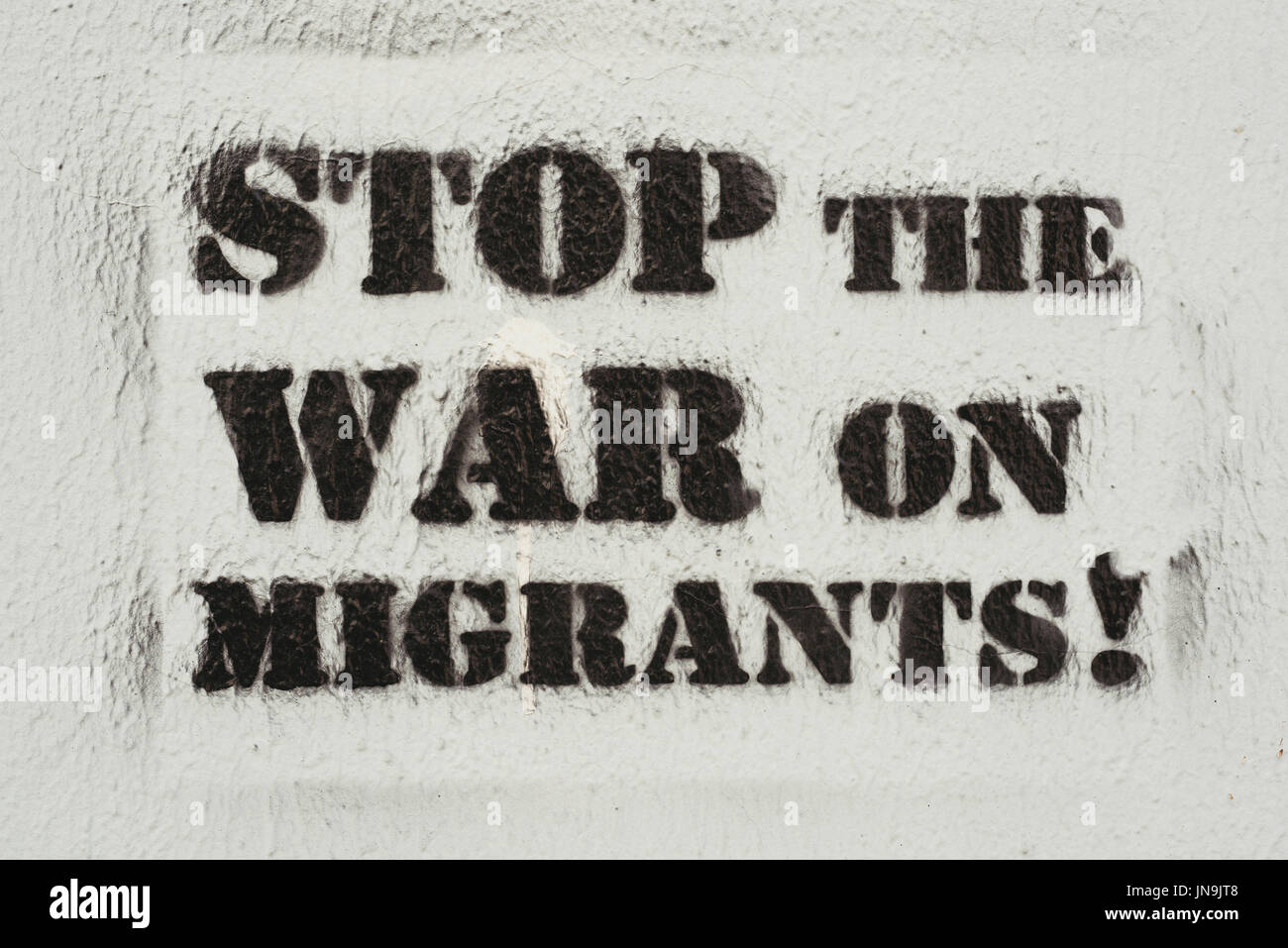 NOVI SAD, SERBIA - JULY 24, 2017: Stop the war on migrants stencil graffiti on the wall - Stock Image