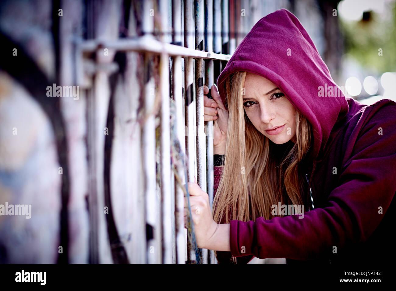 Moody girl in hoody in gritty, urban setting. - Stock Image