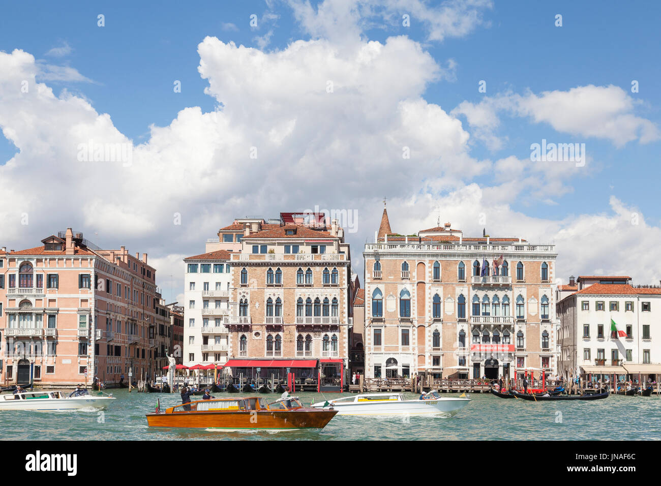 April 2017 Grand Canal, Venice, Veneto, Italy. Boat traffic with water  taxis and gondolas  under dramatic white cumulus clouds passing the Bauer Hote - Stock Image