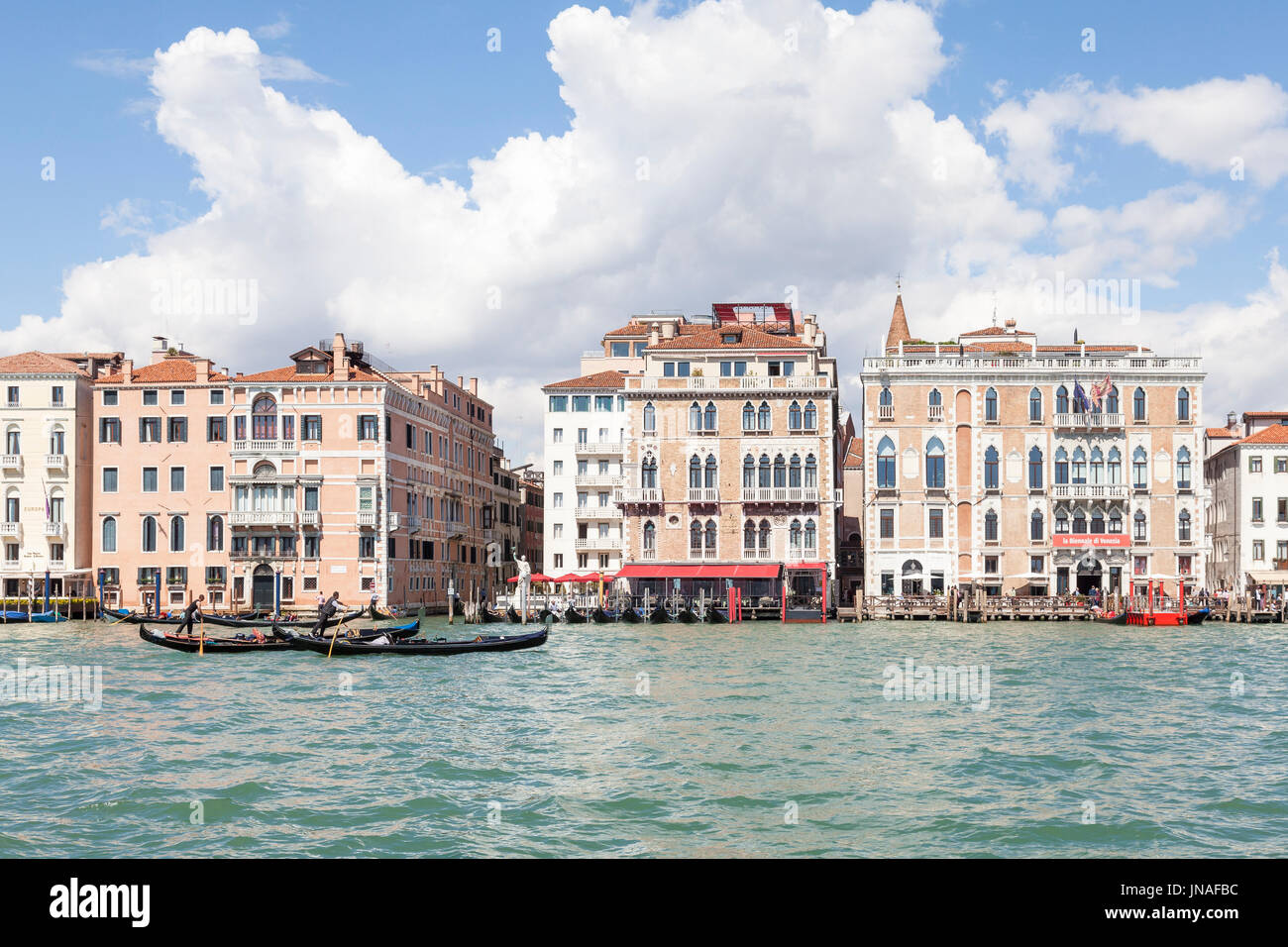 Venice, Veneto, Italy. Gondoliers rowing their gondolas on the Grand Canal past the Hotel Bauer Palazzo and  the Biennale  in the sestiere San Marco,  - Stock Image