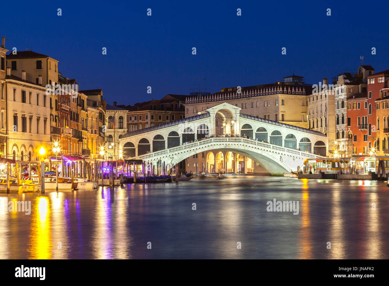 Venice,  Veneto, Italy view of the Rialto Bridge during blue hour with reflections on the water and illuminated Stock Photo